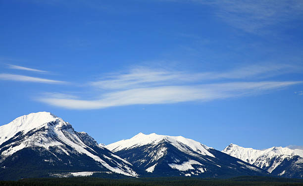 three distant mountains with snow. - british columbia glacier national park stock pictures, royalty-free photos & images
