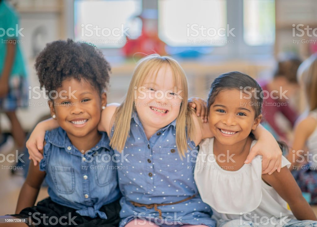 Three diverse friends at kindergarten stock photo