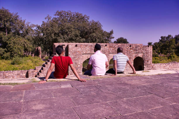 three diverse men sitting on a cliff of abandoned cursed ruined fort in a place named ajabgarh on a way to allegedly haunted place bhangarh fort located in rajasthan india - cursed stock pictures, royalty-free photos & images
