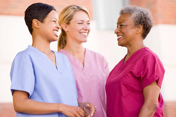 infirmières debout à l'extérieur d'un hôpital - vêtements professionnels hospitaliers photos et images de collection