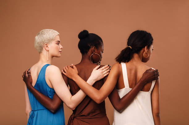 Three diverse women standing against brown background hugging each other stock photo