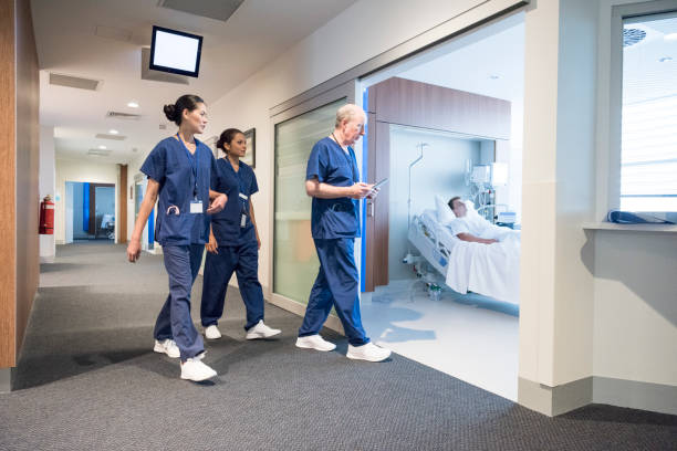 three doctors and nurses walking down hospital corridor and entering ward - australian nurses stock photos and pictures