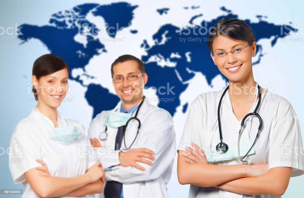 Three doctors in front of a world map royalty-free stock photo