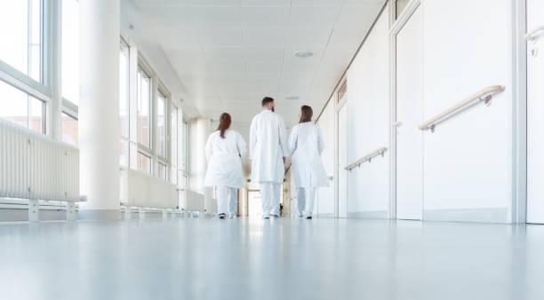 Drei Ärzte zu Fuß einen Korridor im Krankenhaus – Foto
