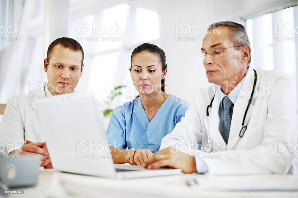 Three doctors working on a laptop. royalty-free stock photo