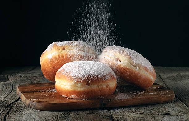 three donut sprinkled with powdered sugar - hausgemachte gebackene donuts stock-fotos und bilder