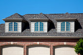 'Three cedar dormers adorn the roof of a three stall garage. Materials  include red brick, asphalt shingles, energy efficient windows, aluminum gutters. Also see these images...'