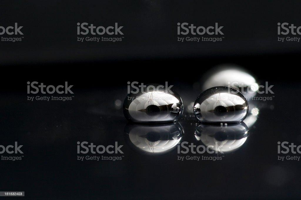 Three drops of mercury lying on a black surface stock photo