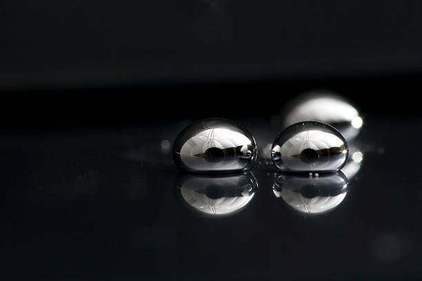 three drops of mercury lying on a black surface - mercury metal stock photos and pictures