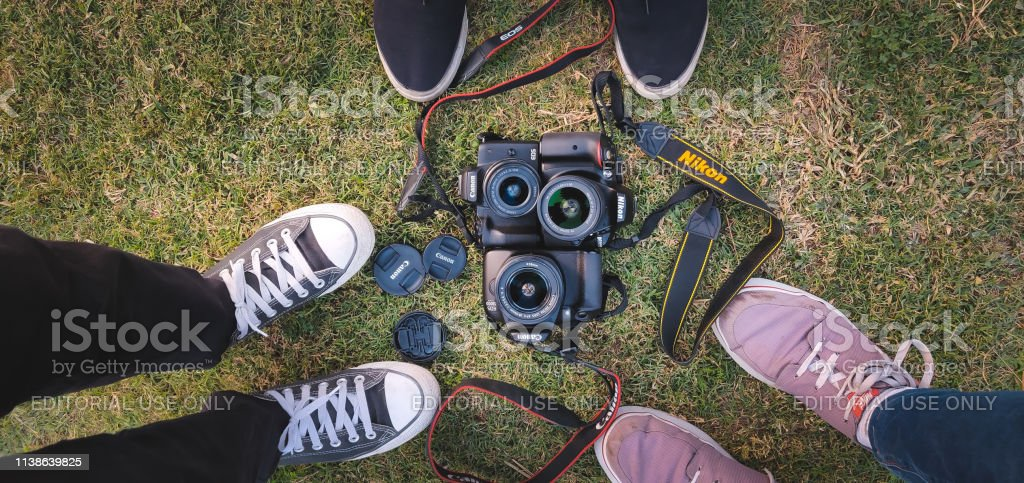 Three DSLRs of Nikon and Canon brand kept on green grass. These two...