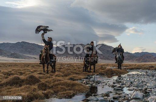 Three eagle hunters  near the river in Mongolia