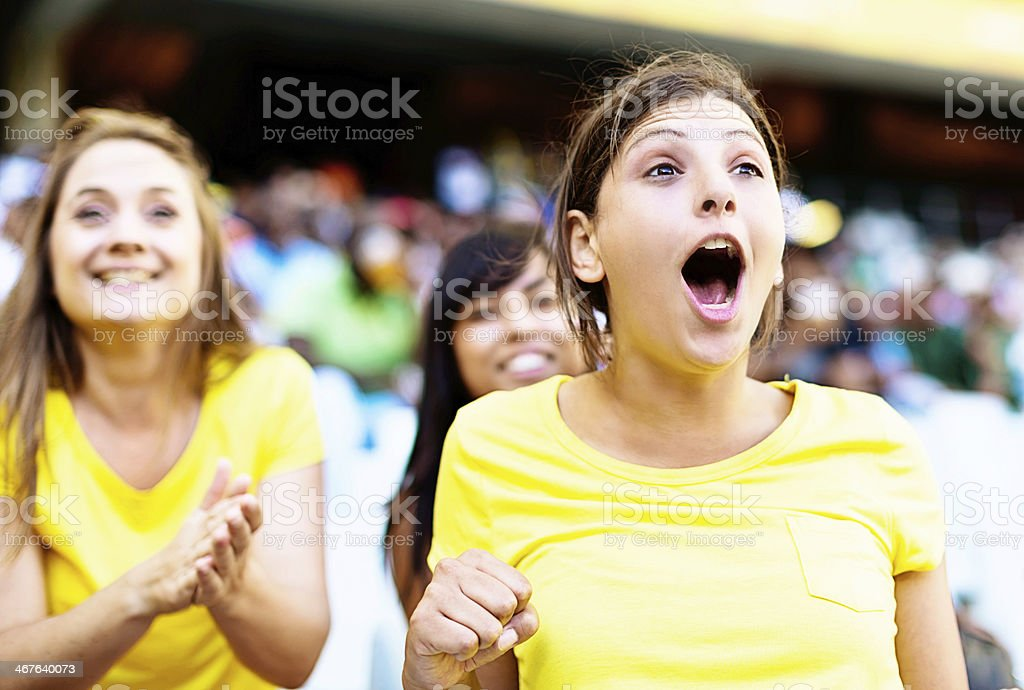 Three ecstatic female soccer fans support thier team stock photo