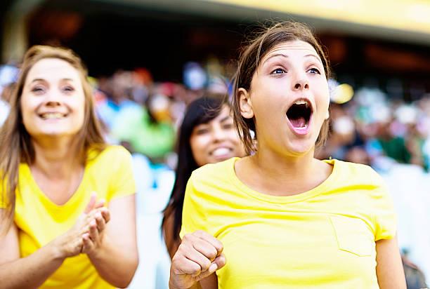 drei weibliche fußball-fans begeistert-support thier - spielerfrauen stock-fotos und bilder