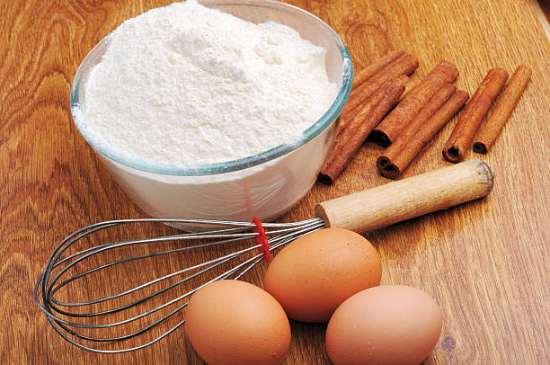 three eggs and flour on a wooden table stock photo