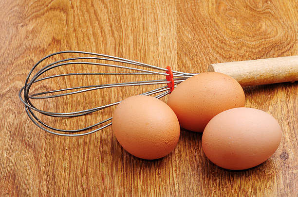 three eggs on a wooden table stock photo