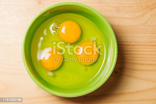 Three raw eggs in a green cup in top view.
