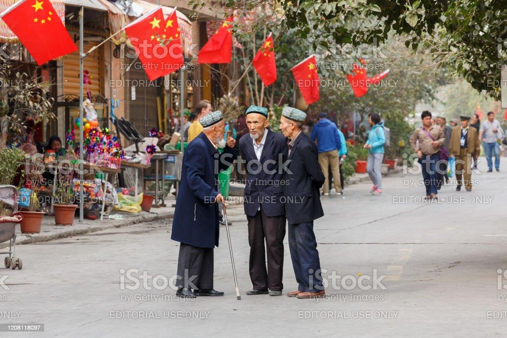 Tres ancianos, hombres uilos teniendo una conversación. En la parte de atrás banderas chinas. - Foto de stock de Adulto libre de derechos