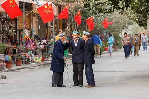 Tres Ancianos Hombres Uilos Teniendo Una Conversación En La Parte De Atrás Banderas Chinas Foto de stock y más banco de imágenes de Adulto