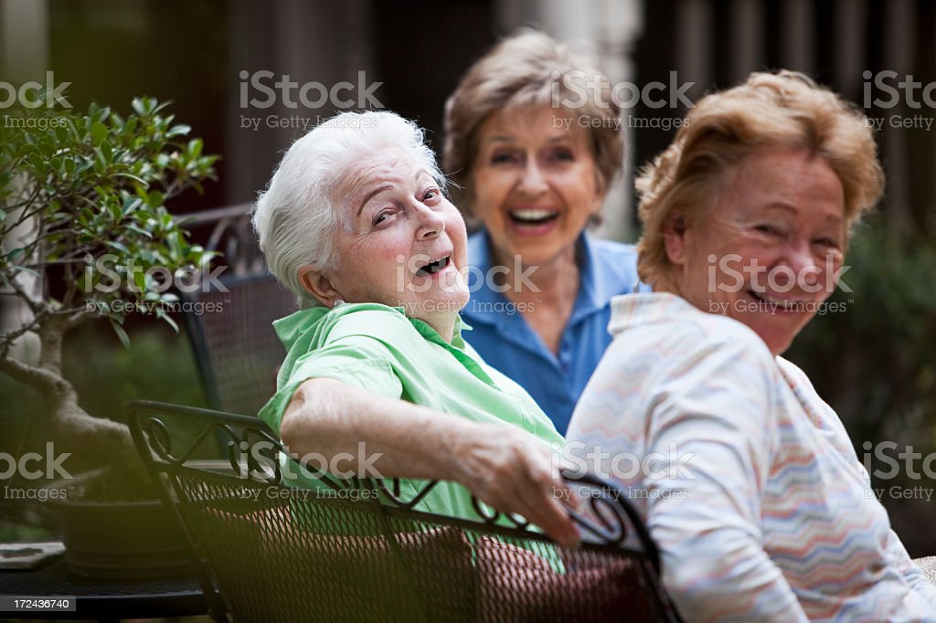 Three elderly women laughing on patio stock photo
