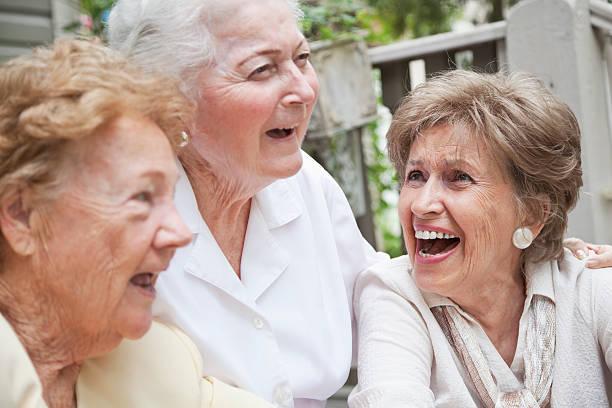Three elderly women laughing stock photo