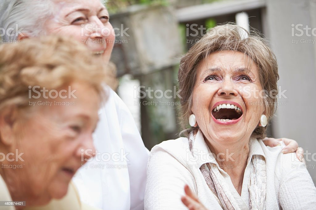 Three elderly women laughing stock photo
