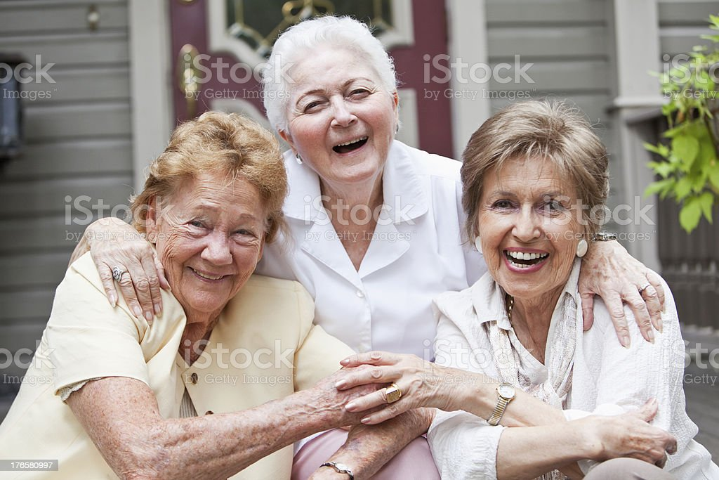 Three elderly women sitting in front of home stock photo