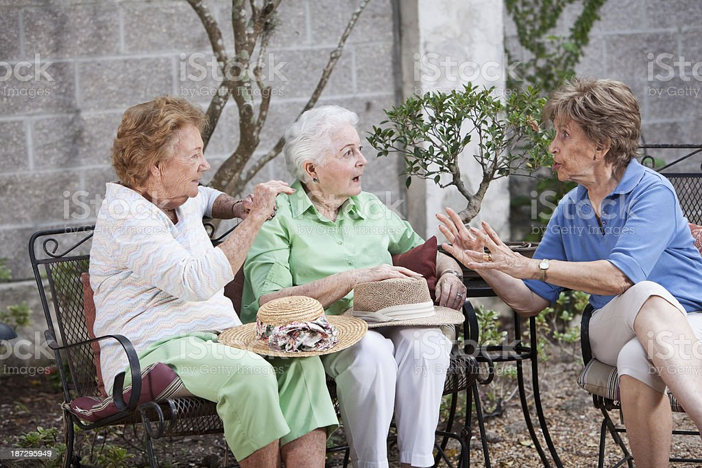 Three elderly women sitting on patio stock photo
