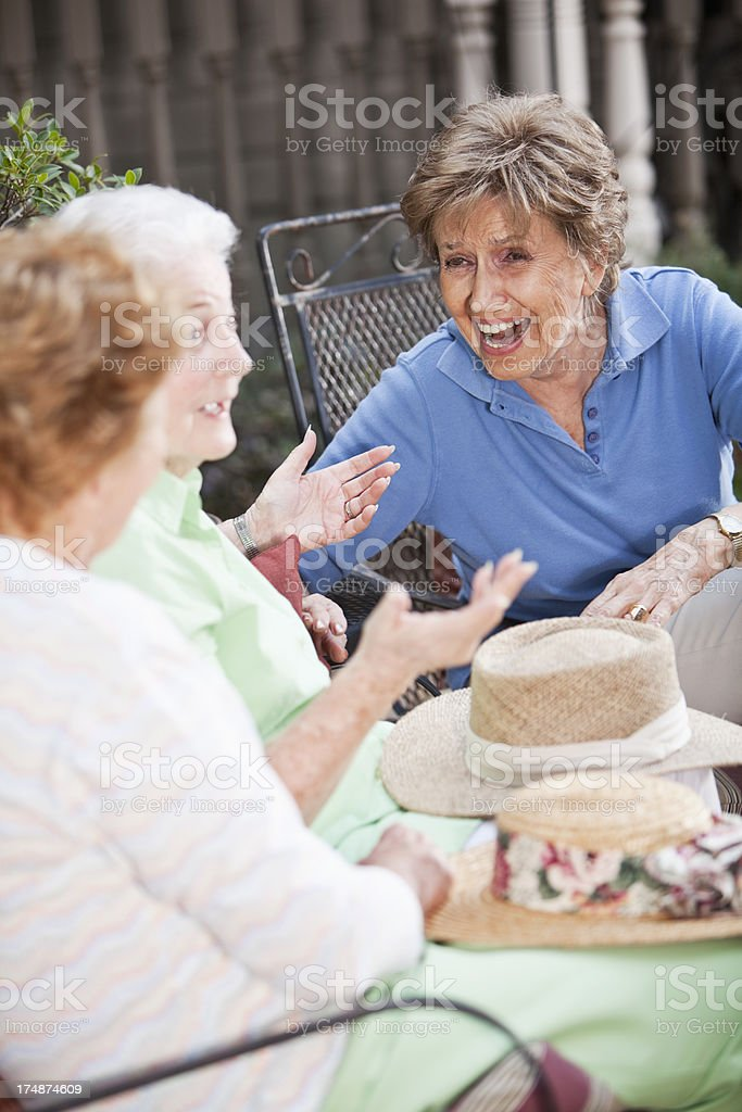 Three elderly women talking on patio stock photo