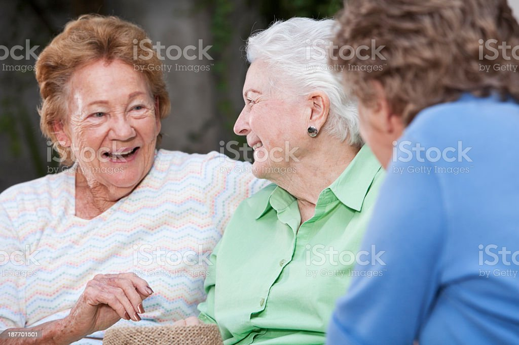Three elderly women talking stock photo