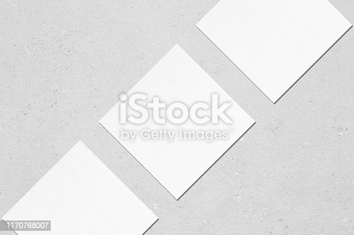1171907064 istock photo Three empty white square business card mockups lying diagonally on light grey concrete background 1170768007