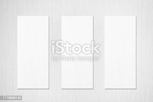 1173565159 istock photo Three empty white vertical rectangle menu mockups with soft shadows on neutral light grey textured wall background 1173565142