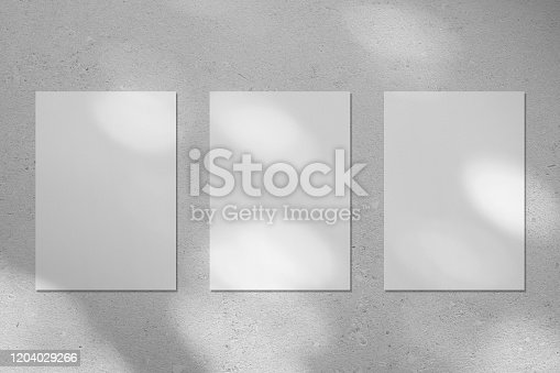 istock Three empty white vertical rectangle poster mockup with diagonal window shadow on the wall 1204029266