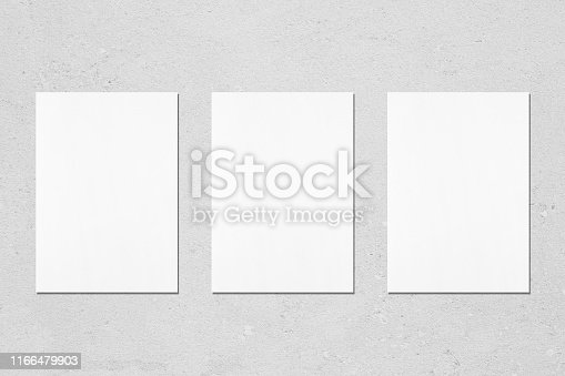 1171907064 istock photo Three empty white vertical rectangle poster mockups on light grey concrete background 1166479903