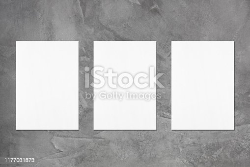 1173565159 istock photo Three empty white vertical rectangle poster mockups 1177031873