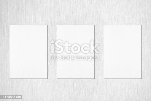 1173565159 istock photo Three empty white vertical rectangle poster or card mockups on neutral light grey textured background 1173565138