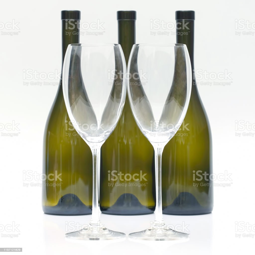 Three empty wine bottles and two glasses on a white background....