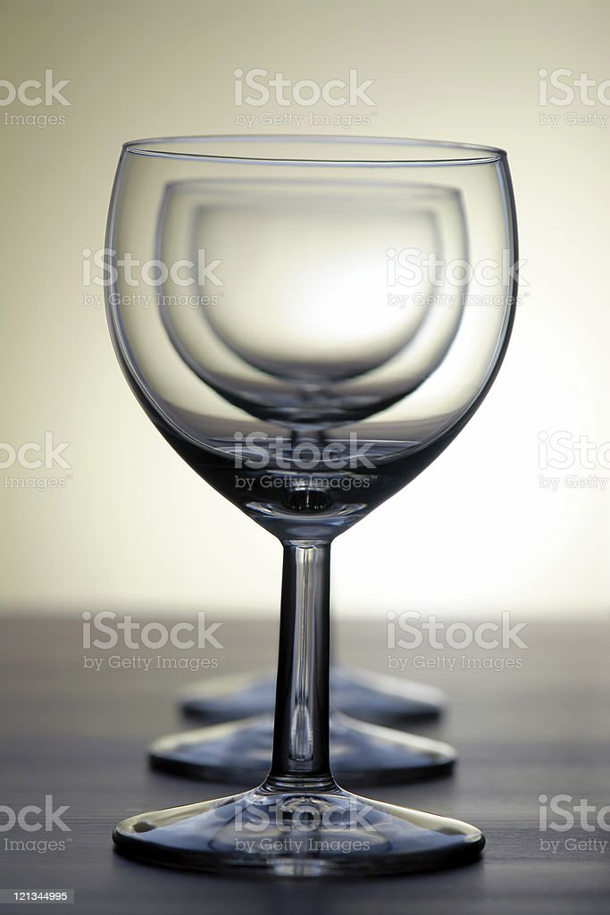 Three empty wine glasses standing on wooden table, golden background royalty-free stock photo