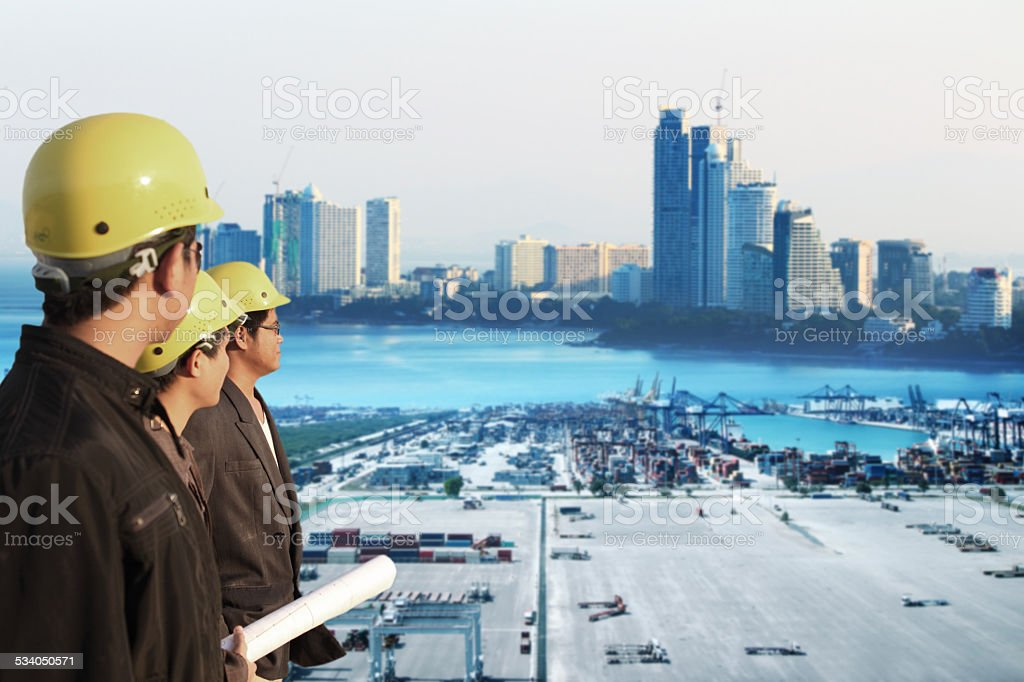 three engineer team standing in front of cranes at the container port...