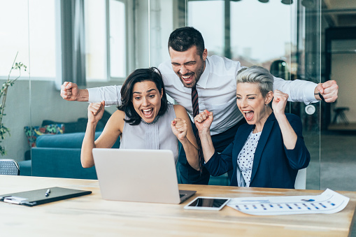 Three excited Business people cheering with arms raised