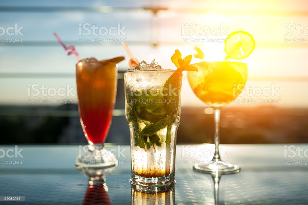 three exotic cocktails in rays of sun; - foto de stock