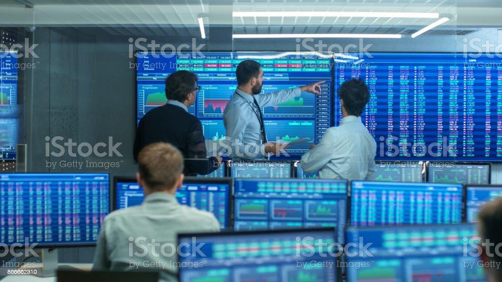 Drei erfahrene Börsenhändler Business reden, Consulting Dokumente und Daten darüber streiten. Sie arbeiten für eine große Börse-Firma. Büro ist voll von Displays zeigen Infografiken und zahlen. – Foto