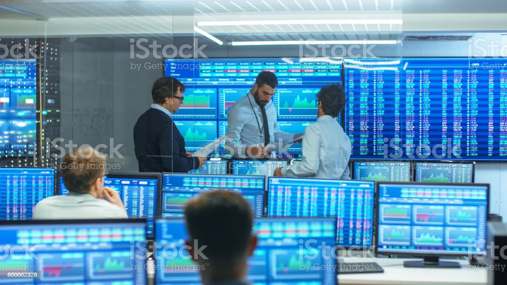 Three Experienced Stock Traders Talking Business, Consulting Documents and Argue About Data. They Work for a Big Stock Exchange Firm. Office is Full of Displays Showing Infographics and Numbers. royalty-free stock photo