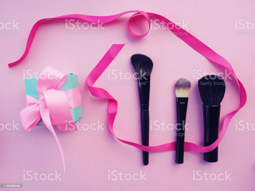 Three Eyeshadow Brushes To Create Makeup On A Pink Background Next To A Satin Ribbon Beauty Industry Woman Flat Lay Makup Background With Cosmetics Cream Lipstick Powder Mascara And Brushes Top View