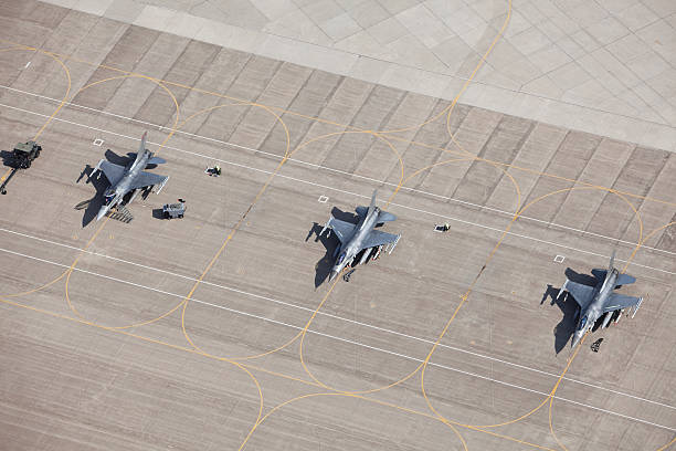Three F-16 Fighter Jets on Tarmac Ready for Flight An aerial view of three F-16 fighter jets sitting on an airfield tarmac ready for flight. All have wing mounted fuel tanks and AMRAMM wingtip (air-to-air) missiles, the left two have Harm (air-to-ground) missiles. The left plane's canopy is open and the safety flags are removed for flight. The left two planes have safety flags in place. Shot from the open window of a small airplane. http://www.banksphotos.com/LightboxBanners/Aerial.jpghttp://www.banksphotos.com/LightboxBanners/Aircraft.jpg airfield stock pictures, royalty-free photos & images
