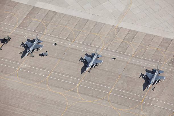 three f-16 fighter jets on tarmac ready for flight - vliegveld stockfoto's en -beelden