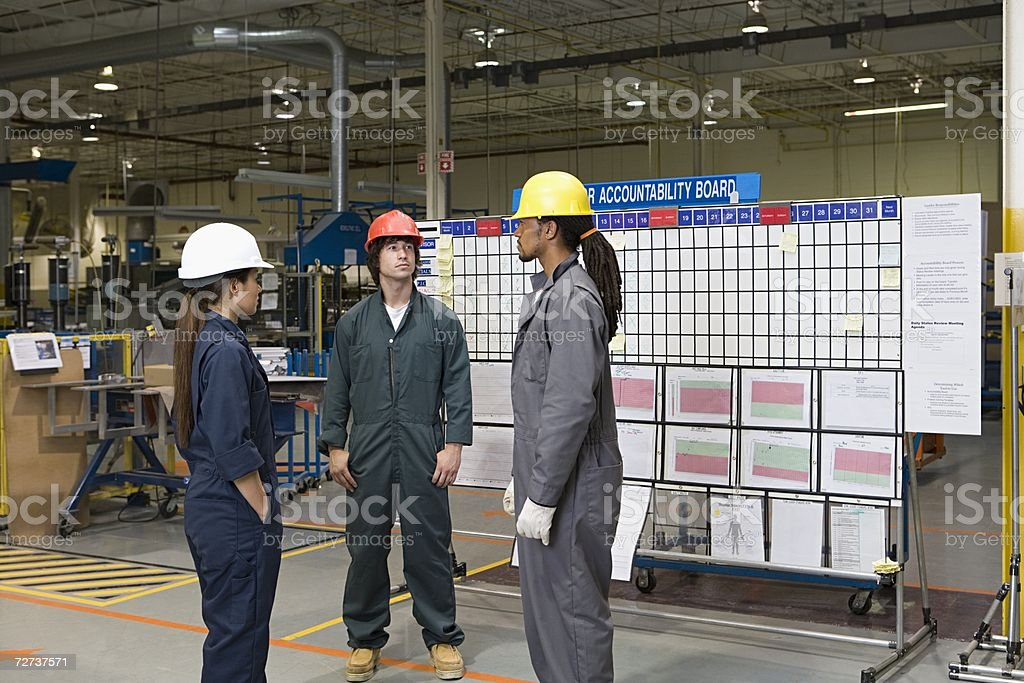 Three factory workers standing near message board stock photo