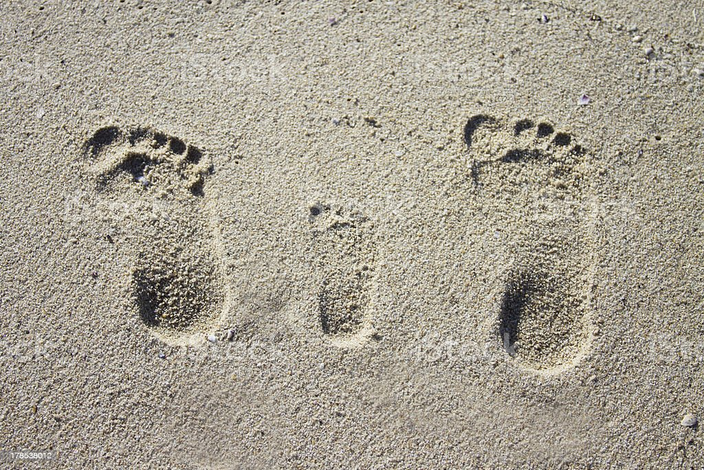 Three family footprints in sand stock photo