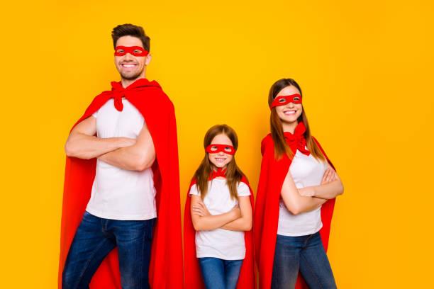 tre familjemedlemmar spelar tecknade otroliga karaktärer bära karneval kostymer isolerad gul bakgrund - superwoman barn bildbanksfoton och bilder