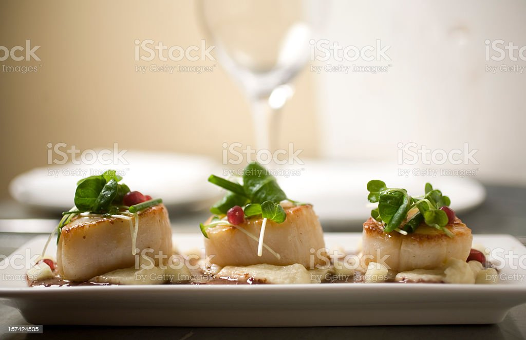 Three fancy scallops on a plate with parsley and sauce stock photo