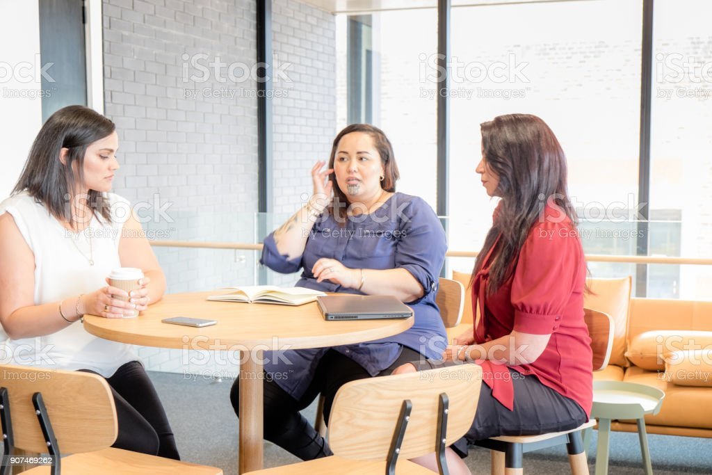 Three female business women in meeting looking serious or anxious. Diversity in work place with mixed caucasian and maori ethnicities. stock photo